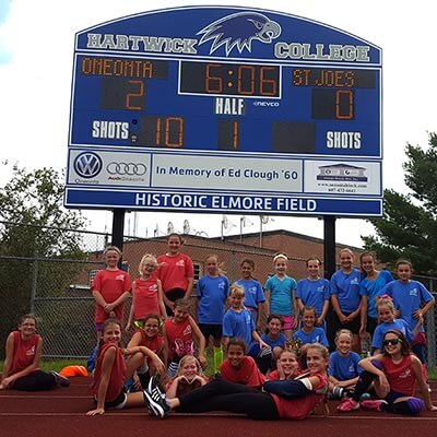 Players pose in front of the large, blue Hartwick scoreboard. The score reads two to zero Oneonta.